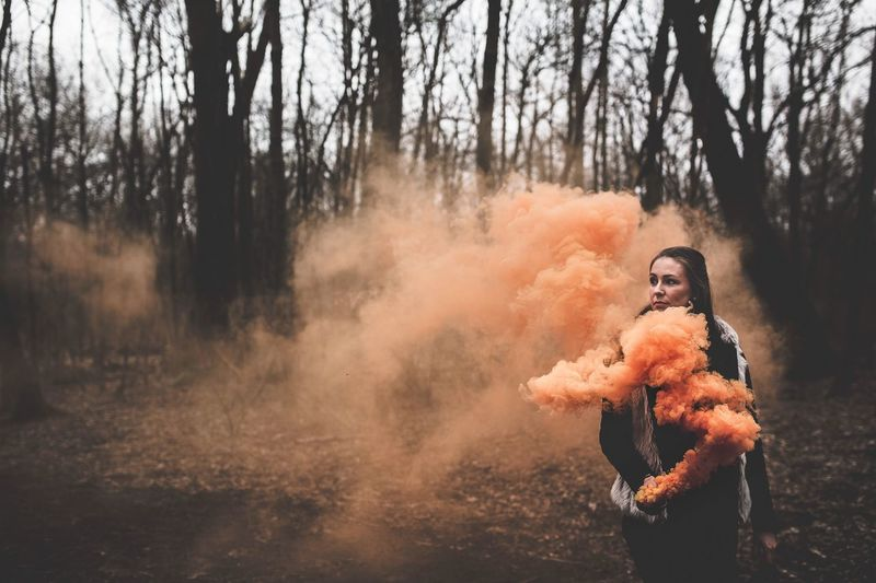 Young woman holding distress flare while standing in forest during winter