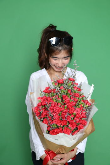 Woman holding red flower against blue background