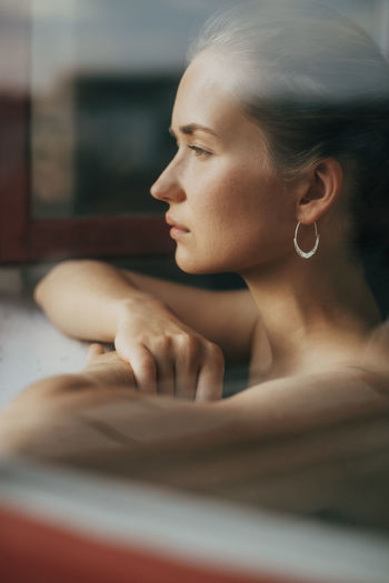 Side view of woman looking away while relaxing in bathtub