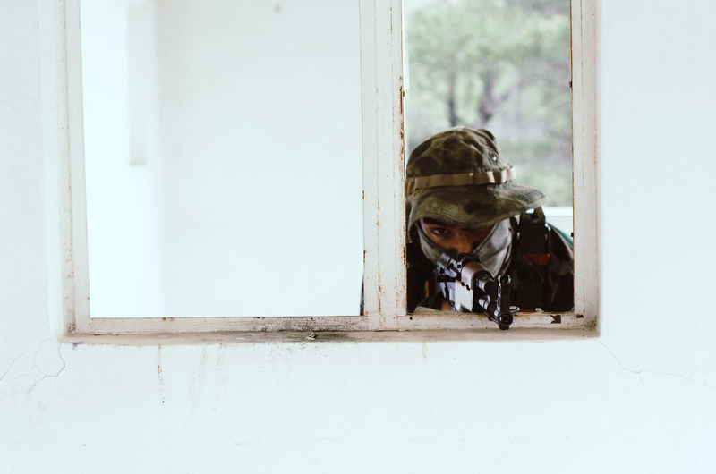 Special forces soldier holding rifle gun aim window white frame cover Window One Animal Day Architecture Glass - Material Mammal Built Structure Transparent No People Outdoors Domestic Entrance Looking Pets Door Domestic Animals Airsoft Sniper Trooper Soldier Army Army Soldier Special Forces Aim Aiming Camouflage Clothing Camouflage Hat AK 47 Gun