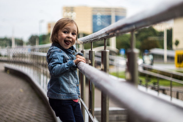 Architecture Casual Clothing Child Childhood Day Emotion Footbridge Girls Happiness Innocence Leisure Activity Lifestyles Mouth Open One Person Outdoors Portrait Railing Real People Smiling Standing