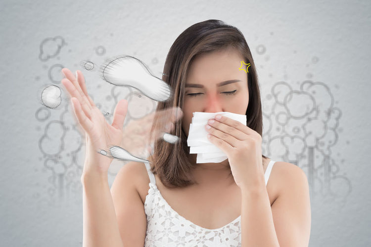Digital composite image of woman sneezing over white background