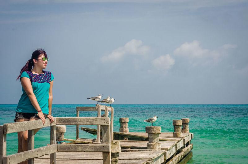 Boy on sea against sky