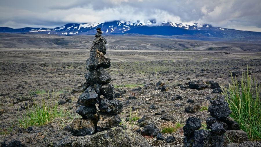 Stack Of Rocks On Field Against Cloudy Sky