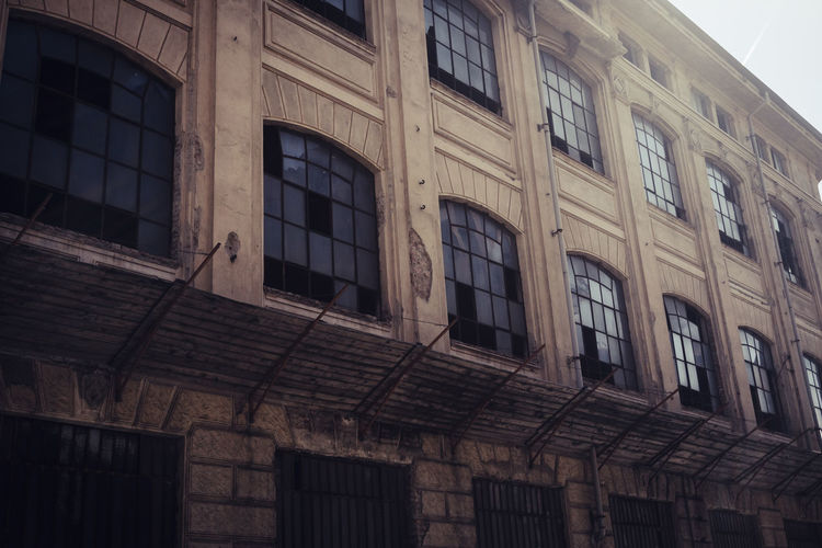 abandoned place in town, retro dark horror filter and concept Broken Windows Dark Fear Horror Zombie Abandoned Building Building Exterior Built Structure City Day History In A Row Low Angle View Movıe No People Old Outdoors Repetition Side By Side Sky Spectral The Past Town Window