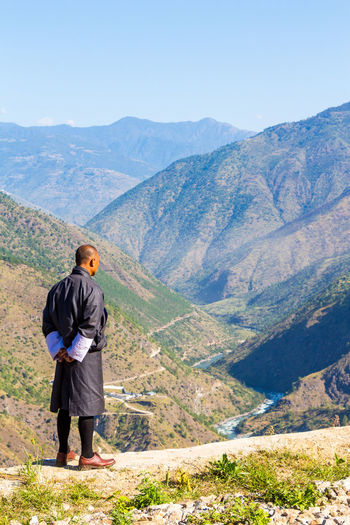 ASIA Man Traditional Clothing Activity Adult Adventure Beauty In Nature Bhutan Day Environment Full Length Hiking Landscape Looking At View Mountain Mountain Range Nature Non-urban Scene One Person Outdoors Rear View Scenics - Nature Travel