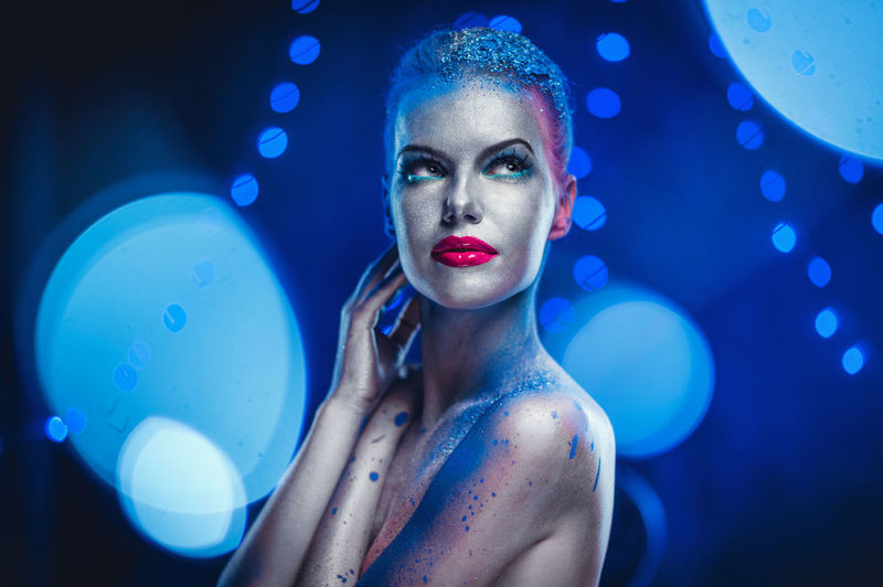 Thoughtful Naked Woman With Glitter Against Blue Background