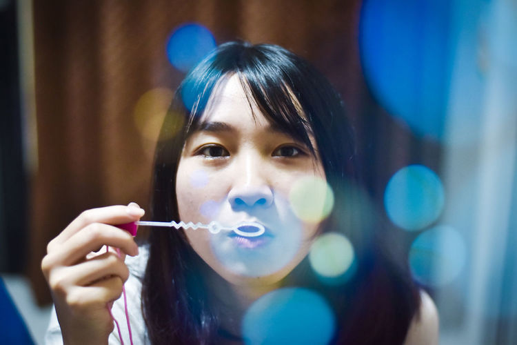 Young woman blowing bubbles at home