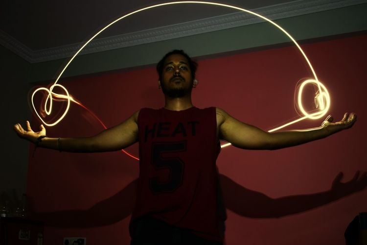 Low angle view of man standing with arms outstretched by light painting at home