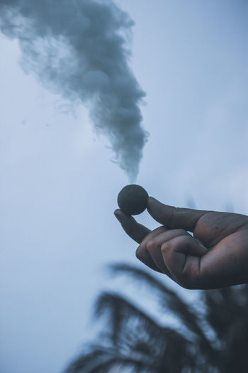 Cropped hand of person holding firework with smoke against sky