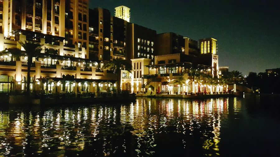 Illuminated buildings by lake in city at night