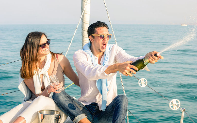 Young couple in love on sailing boat cheering with champagne wine bottle - Happy girlfriend birthday party cruise travel on luxury sailboat - Focus on boyfriend face with sunny afternoon color tones Couple Love Luxury Travel Sailboat Sailing Boat Boat Sailing Anniversary Rich Lifestyle People Yacht Sail Young Happy Summer World Wanderlust Champagne Wine Celebrating Cheers Birthday Party