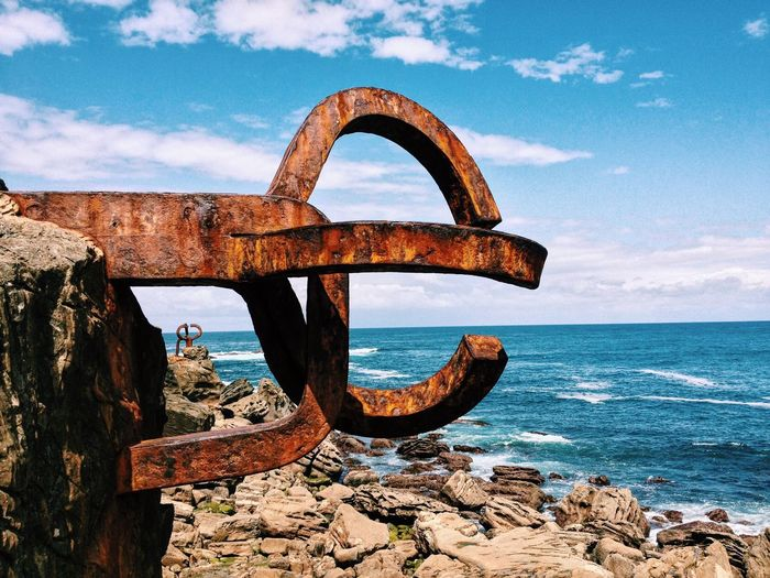 Old rusty anchor by rocky seashore against sky