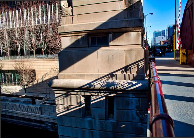 Shadows of bridge cast across concrete bridgehouse located on LaSalle Street Bridge in downtown Chicago's Loop. Waysofseeing Architecture Care Caution Chicago Chicago River Chicago Loop Downtown Chicago Exterior Lasalle Street Lines Streetlamp Tree Architecture Barrier Bridge - Man Made Structure Building Building Exterior Built Structure City Concrete Design Fence Riverwalk Shadow Streetlight