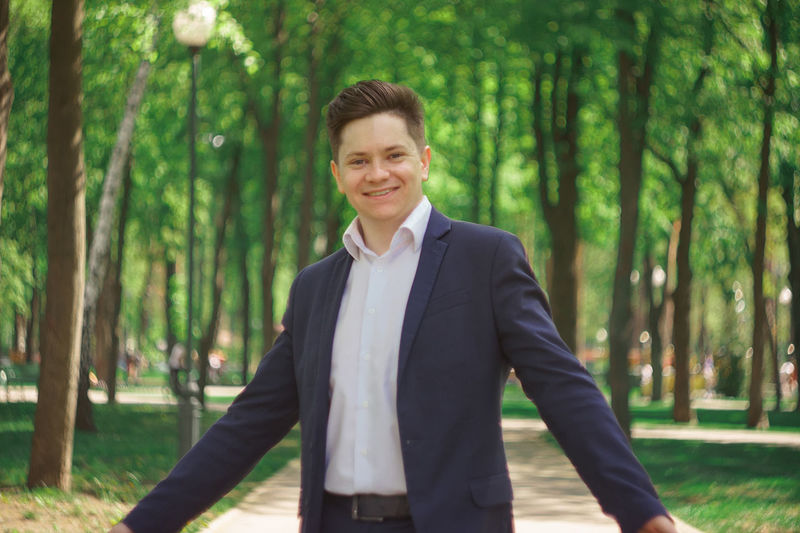 Portrait of smiling young businessman with arms outstretched standing in park