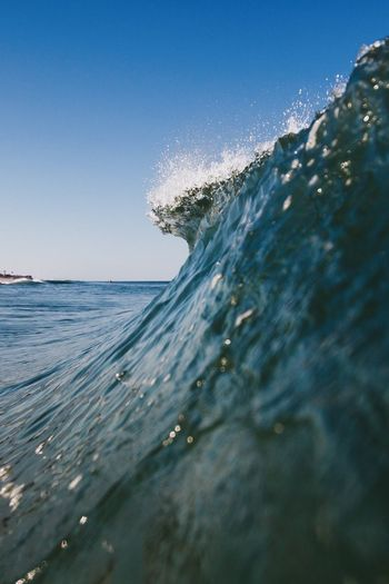 Waves in sea against clear blue sky