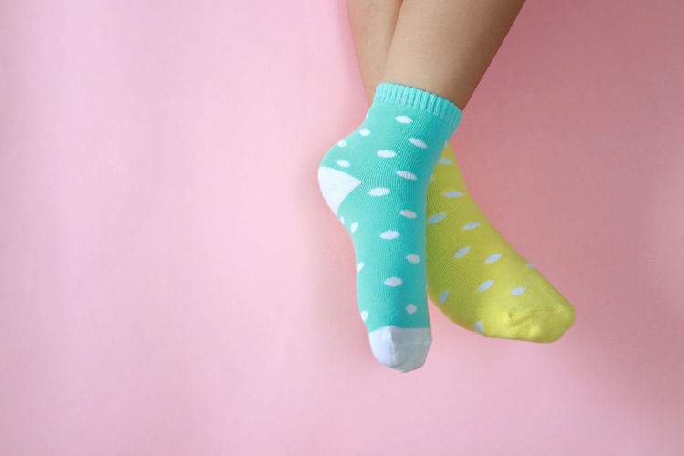 Low Section Of Woman Wearing Socks Against Pink Background