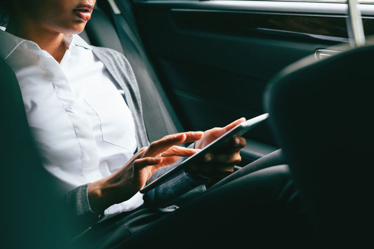 Business Businesswoman Car Car Interior Close Up Communication Connection Digital Tablet Female Formal Holding Journey Land Vehicle Modern Portability Portable Information Device Technology Text Messaging Touch Screen Transportation Unrecognizable Person Vehicle Interior Wireless Technology