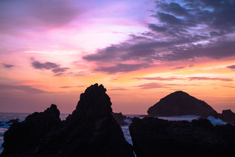 Silhouette rocks by sea against romantic sky at sunset