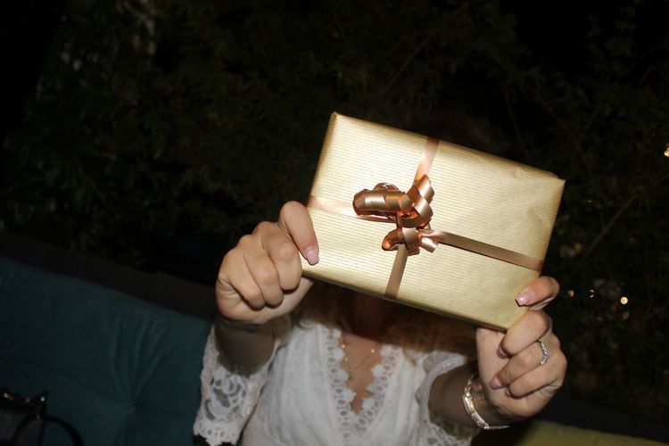 Woman covering face with gift box at night