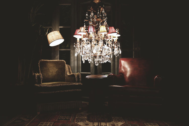 Illuminated chandelier hanging by armchairs in darkroom