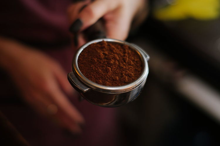 Cropped hand of women holding coffee powder in porta filter