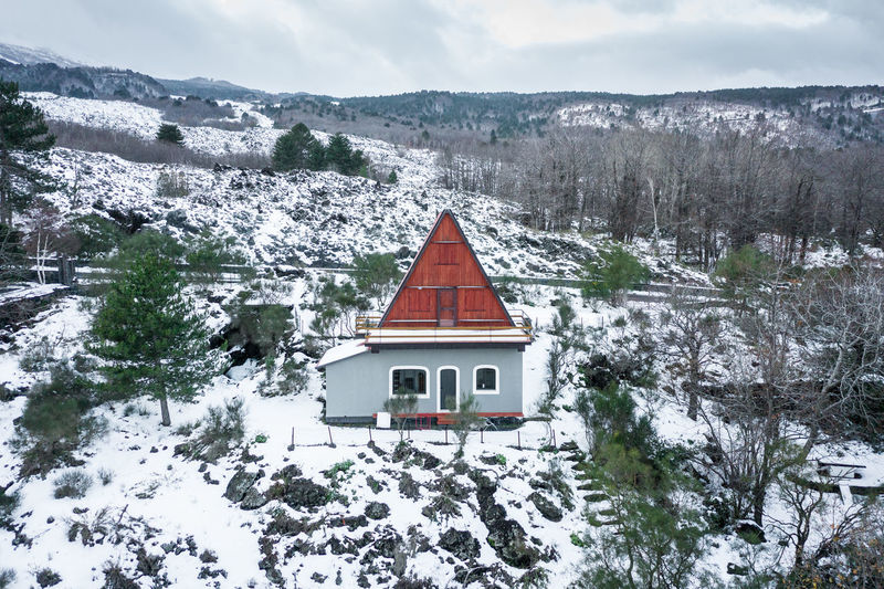 House on snow covered field by building