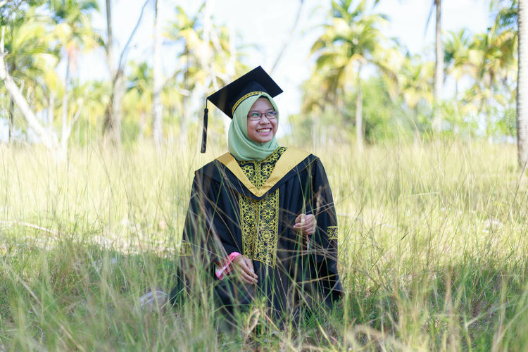 Smiling young woman wearing graduation gown while standing on field