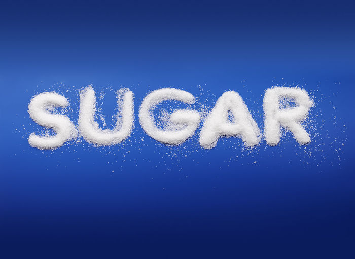 Word Sugar written with real fine granulated sugar on blue background. Text Blue No People Colored Background Studio Shot Copy Space White Color Capital Letter Single Word Blue Background Sugar Sweet