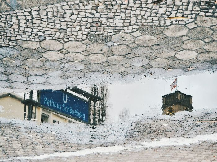 Buildings reflecting in puddle on street