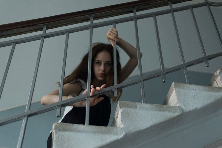 Woman looking at railing against sky