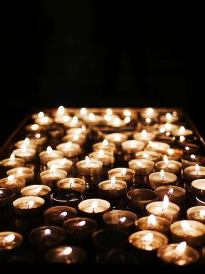 Close-up of illuminated tea light candles in temple