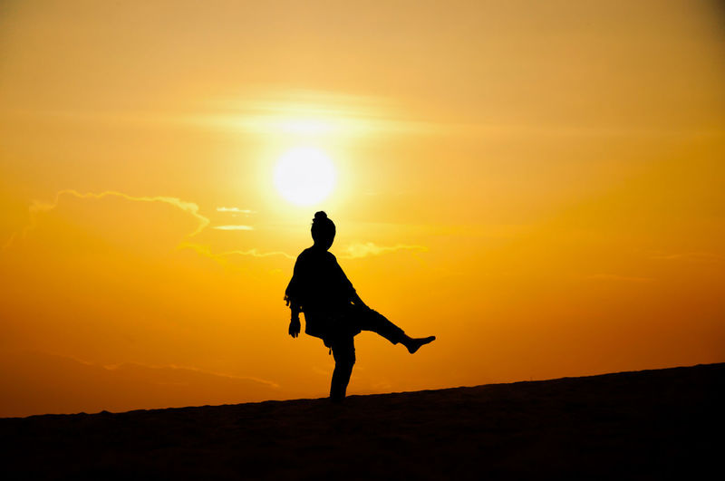 Silhouette woman standing on one leg at beach against orange sky during sunset