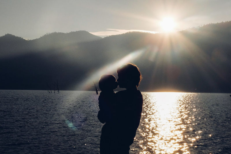 Beauty In Nature Family Family Time Holding Kiss Lake Leisure Activity Lifestyles Love Mountain Mountain Range Nature Non-urban Scene Person Scenics Silhouette Standing Sun Sunbeam Sunlight Sunny Tranquil Scene Tranquility Vacations Water