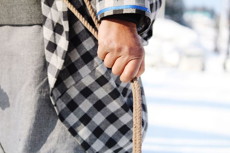 Midsection of man holding rope