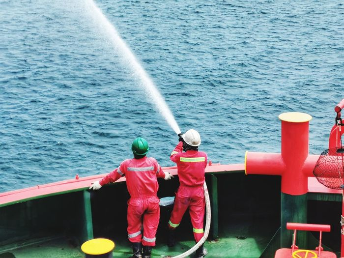 Rear view of firefighters spraying water while standing in nautical vessel