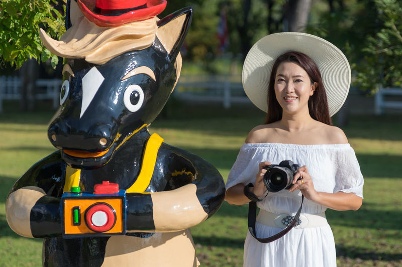 San Kamphaeng, Chiang Mai / Thailand - Nov 06 2018 : Beautiful Asian girl relaxing in the resort wearing a white dress, holding a camera, Acting same horse mascot at dutch Farm Chiang Mai. Adult Asian  Attractive Background Beautiful Beauty Breathing Calm Casual Charming Closeup Cute Dress Face Female Field Free Freedom Girl Grass Green Happiness Happy Headphones Health Healthy Hipster Life Lifestyle Long Nature Outdoor Outdoors Outside Park People person Portrait Pretty Relax Relaxation Relaxing Smile Spring Summer Sun Wellness White Woman Young