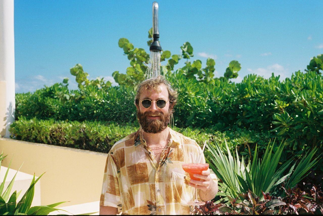 Portrait of man drinking cocktail under shower