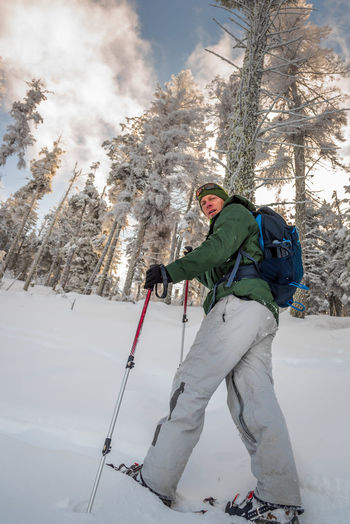 Low angle view of man skiing on snow covered land