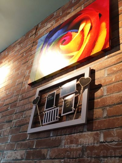Painting on the bricks wall of a restaurant. Frame Painting Low Angle View No People Architecture Brick Wall Built Structure Window Multi Colored Building Exterior