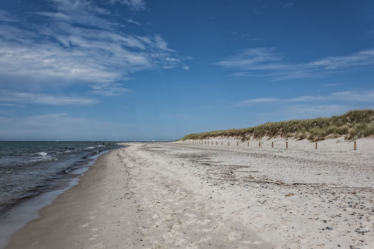 Scenic View Of Empty Beach Against Blue Sky