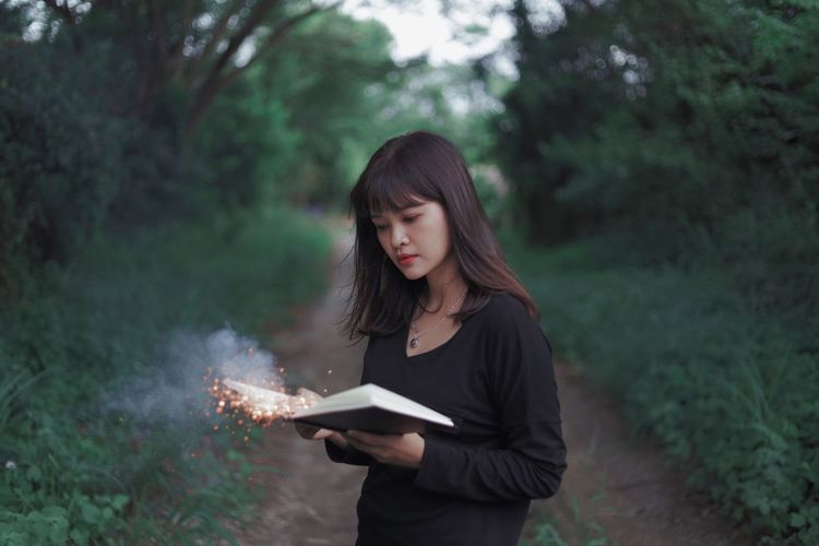 Portrait of woman holding sparklers in book while standing in forest
