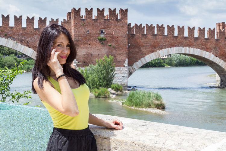 Smiling young woman using phone at castelvecchio