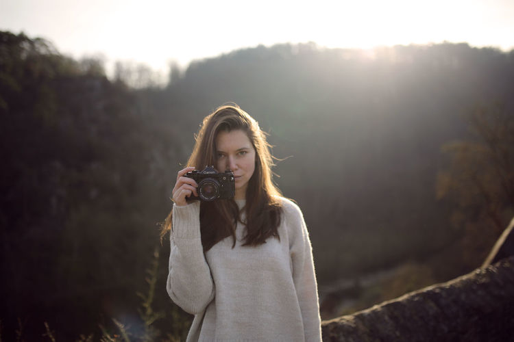 Winter sun One Person Standing Leisure Activity Holding Hairstyle Long Hair Lifestyles Beautiful Woman Front View Portrait Hair Telephone Wireless Technology Outdoors Lens Flare Burg Eltz Autumn Sweater Backlight Girl Woman Camera Winter Sun Young Adult Real People