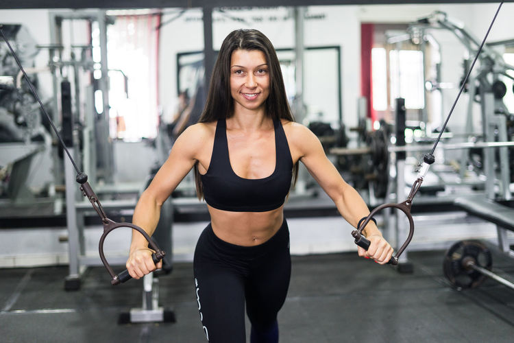 Adult Body Conscious Effort Equipment Exercise Equipment Exercising Focus On Foreground Front View Gym Health Club Healthy Lifestyle Indoors  Lifestyles Looking At Camera Muscular Build One Person Smiling Sport Sports Clothing Sports Training Strength Vitality Weight Weight Training  Women
