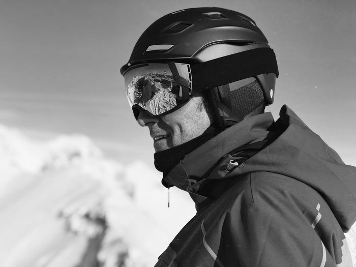 Side View Of Smiling Mature Man Wearing Ski Helmet Against Sky