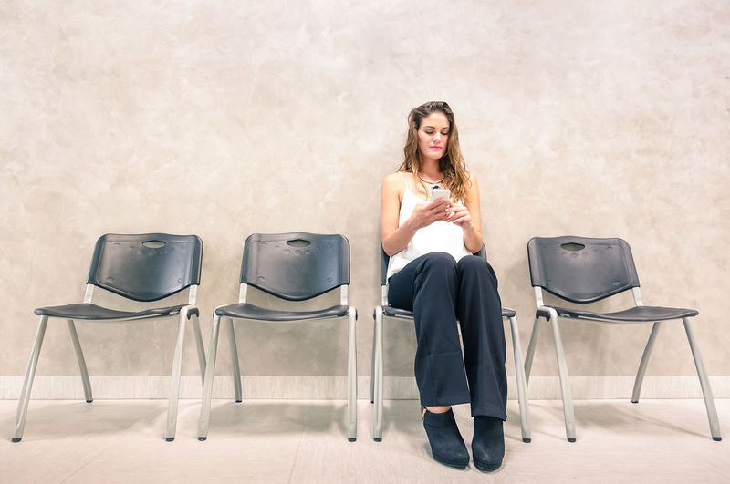 Woman sitting on chair against wall