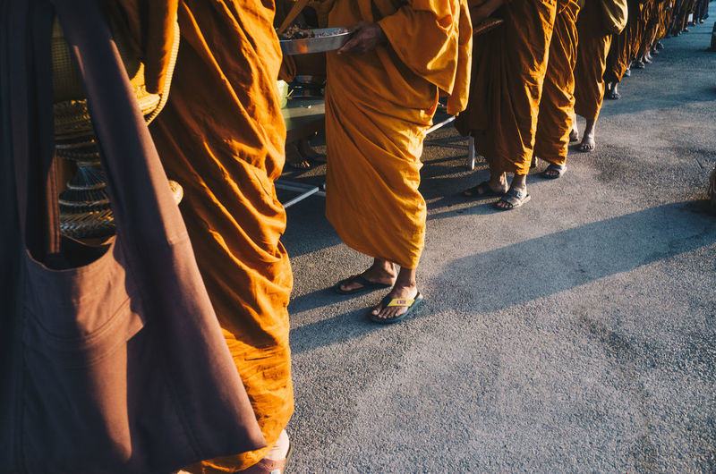 Low section of monks standing outdoors