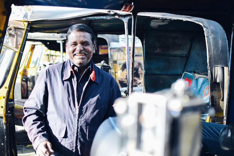 Portrait of smiling man standing against rickshaw