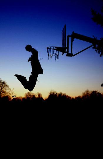 Silhouette of man playing basket